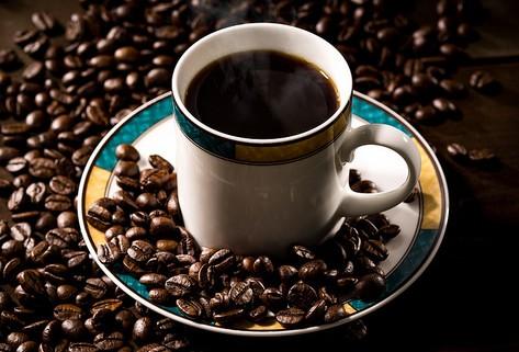 淹れたてのブラックコーヒーと散りばめられたコーヒー豆