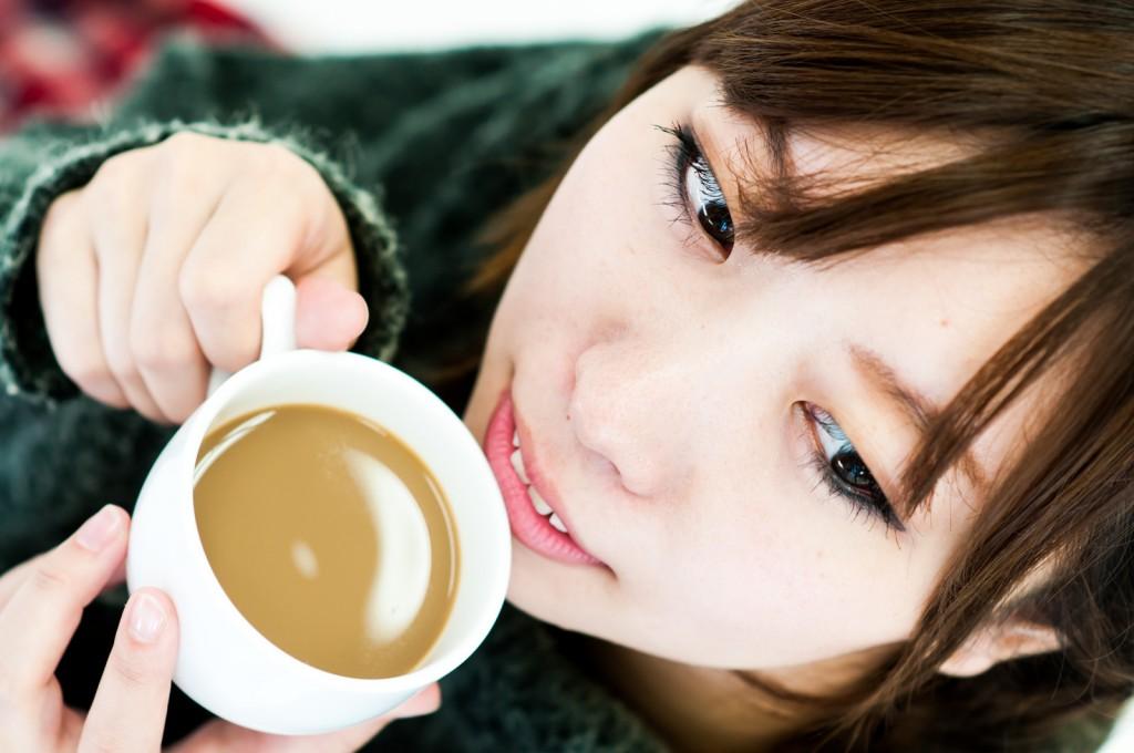 コーヒーを口へ運ぶ女性